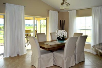 Long side panels hung high complement to view beyond - Interior Design - in the Villages of Florida.